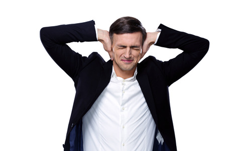 hands over ears: Businessman holding hands on the ears over white background