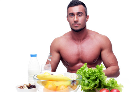 staring at the camera man: Handsome muscular man sitting at the table with healthy food Stock Photo
