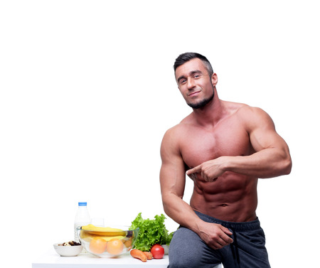 Gelukkig gespierde man wijst op gezond voedsel Stockfoto