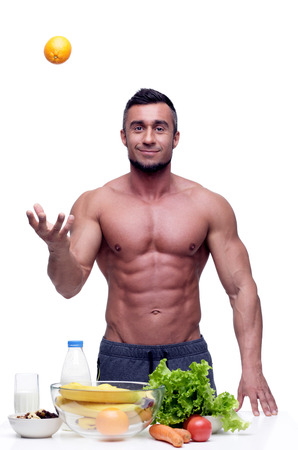 healthy men: Cheerful muscular man standing with healthy food