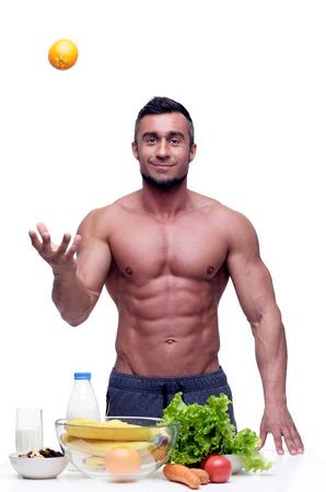 hombre comiendo: Muscular hombre alegre que se coloca con la comida sana