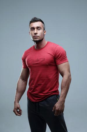 uomo rosso: Grave uomo muscoloso in rosso t-shirt in piedi su sfondo grigio Archivio Fotografico