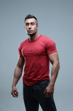 stylish man: Serious muscular man in red t-shirt standing over gray background