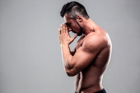 Retrato de un hombre musculoso joven rezando sobre fondo gris Foto de archivo