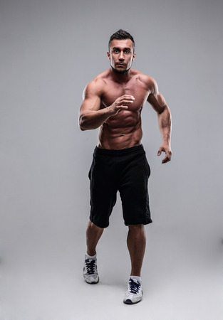 Portrait of a muscular man running over gray background