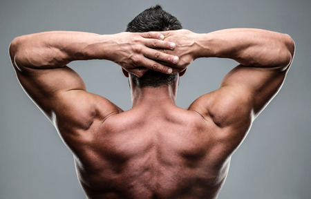 Closeup portrait of a muscular mans back over gray background