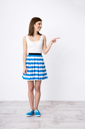 Full length portrait of a happy woman pointing away photo
