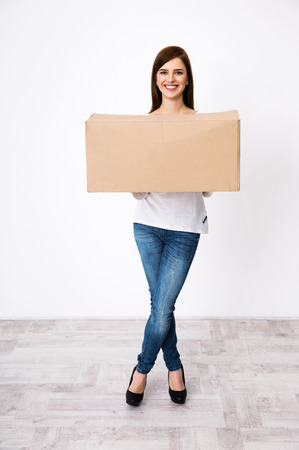 Full length portrait of a smiling woman standing with box photo