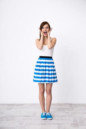 Full length portret van een jonge verraste vrouw Stockfoto