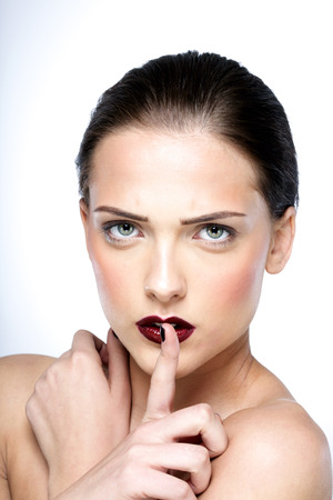 hushed: Beauty portrait of attractive woman making a hush gesture