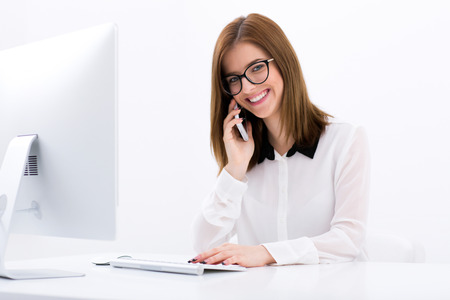 Happy businesswoman talking on the phone at office