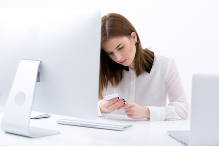 concetrated: Young beautiful businesswoman sitting at the table in office and using smartphone