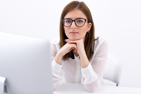 Portrait of a pensive businesswoman sitting at her workplace in office photo