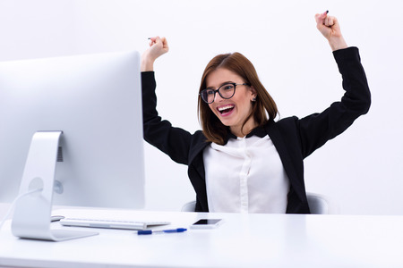 excited: Excited businesswoman rejoicing at her success cheering and raising her fists in the air Stock Photo