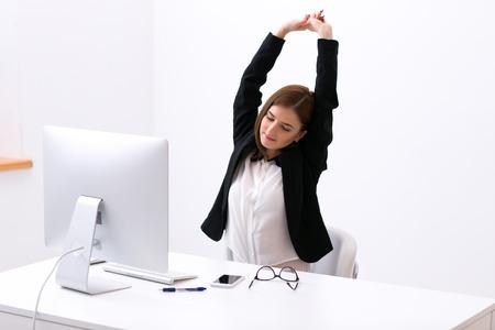実業家のオフィスでテーブルに座っていると彼女の頭の上に彼女の手を伸ばす