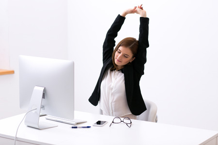 Businesswoman sitting at the table in office and stretching her hands above her head Stock Photo