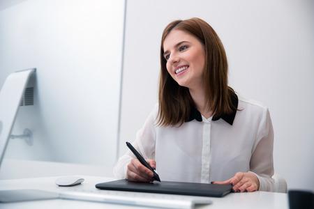 monitor de computadora: Sonre�r editor de fotos femenina trabaja en el ordenador en la oficina
