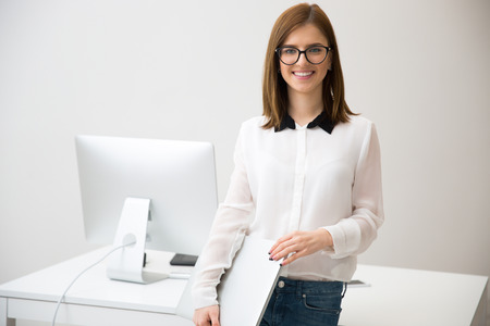 Smiling beautiful businesswoman standing with laptop in front of her workplace