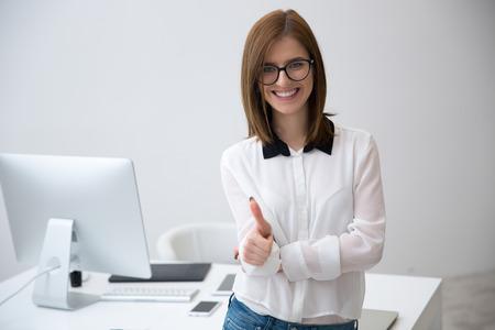Vrolijke zakenvrouw staat met duim omhoog in het kantoor