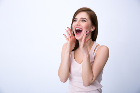 screaming face: Portrait of a surprised young woman over gray background