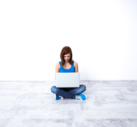 concetrated: Young beautiful woman sitting at the floor and using laptop