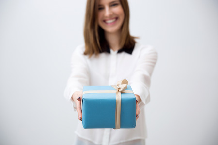 wrapped present: Smiling young woman giving gift. Focus on a gift Stock Photo