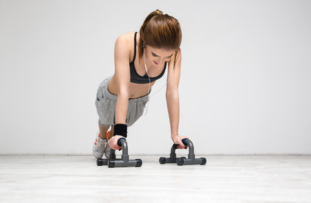 sexy teen: Young beautiful woman doing push ups at gym Stock Photo