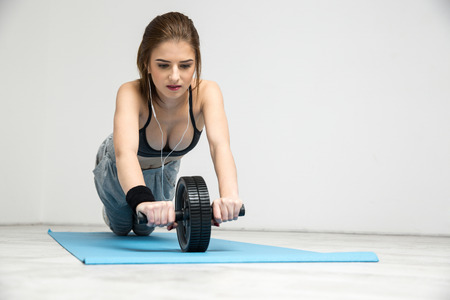 concetrated: Young woman exercising fitness workout abdominal wheel