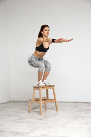 squatting down: Young healthy woman doing squat exercises