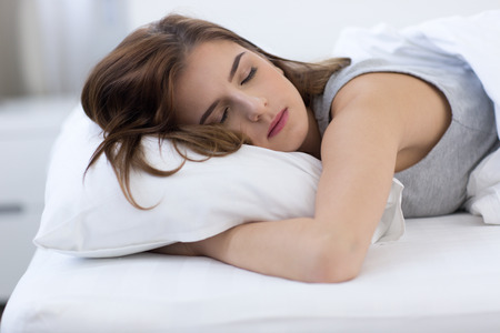 ojos hermosos: Retrato de una mujer dormida en la cama en su casa