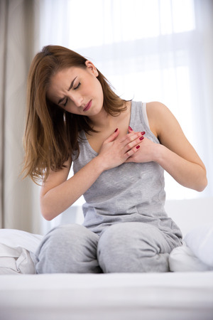 chest pain: Young woman in pajamas having pain in heart