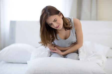 human stomach: Young woman sitting on the bed with pain