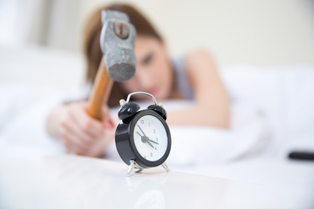 bother: Woman not wanting to get up, taking a hammer to her alarm clock. Focus on clock