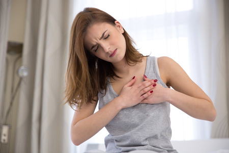 human chest: Young woman in pajamas having heart attack Stock Photo
