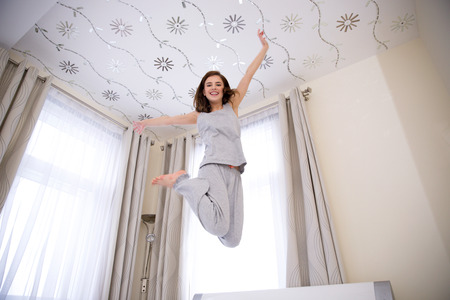 Portrait of a young happy woman jumping on the bed Reklamní fotografie