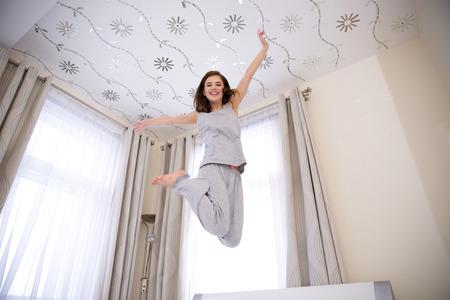 saltando: Retrato de una joven mujer feliz saltando en la cama