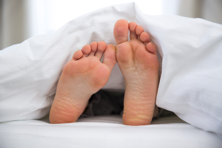Feet of a young woman on the bed photo
