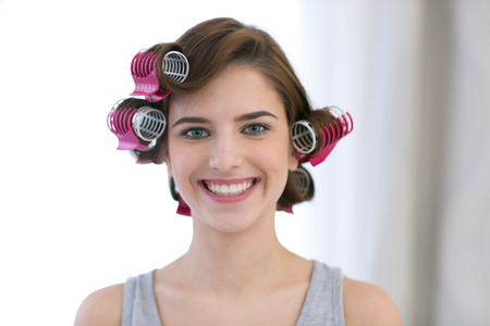 curled lip: Portrait of a smiling woman with curlers on her head