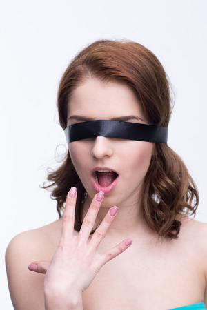 Surprised woman with black blindfold over gray background photo