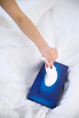 snot: Closeup image of a female hand pulls out a napkin from the box
