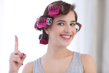 curled lip: Portrait of a happy woman with curlers on her head pointing finger up