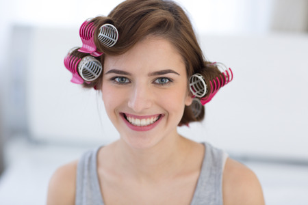 curled lip: Portrait of a happy woman with curlers on her head