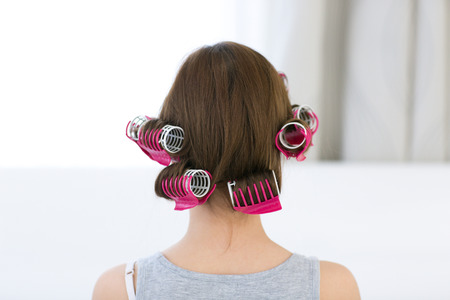 Back view portrait of a woman with curlers on her head photo