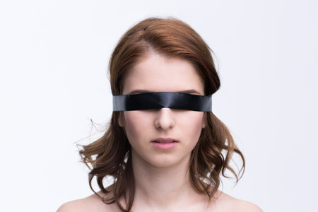 Blindfold young woman over gray background photo