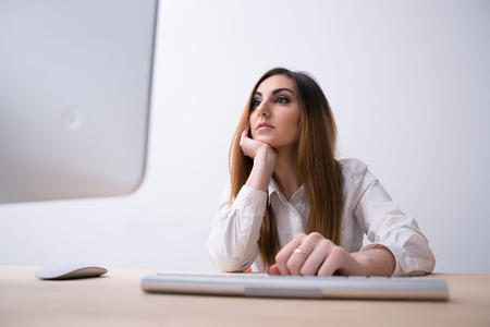 concetrated: Young beautiful woman looking at monitor in office