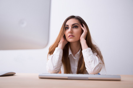 concetrated: Pensive business woman sitting at the table with computer