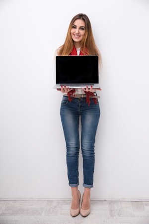 Full length portrait of a happy woman showing blank laptop screen photo