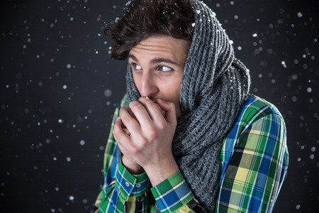 Young handsome man looking away with snow on background