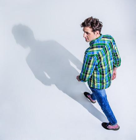 경치: 회색 backgorund에 걷고 다채로운 착용에 젊은 남자의 상위 뷰 초상화