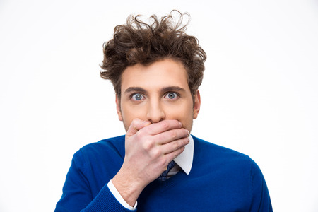 coward: Portrait of a young man covering his mouth over white background